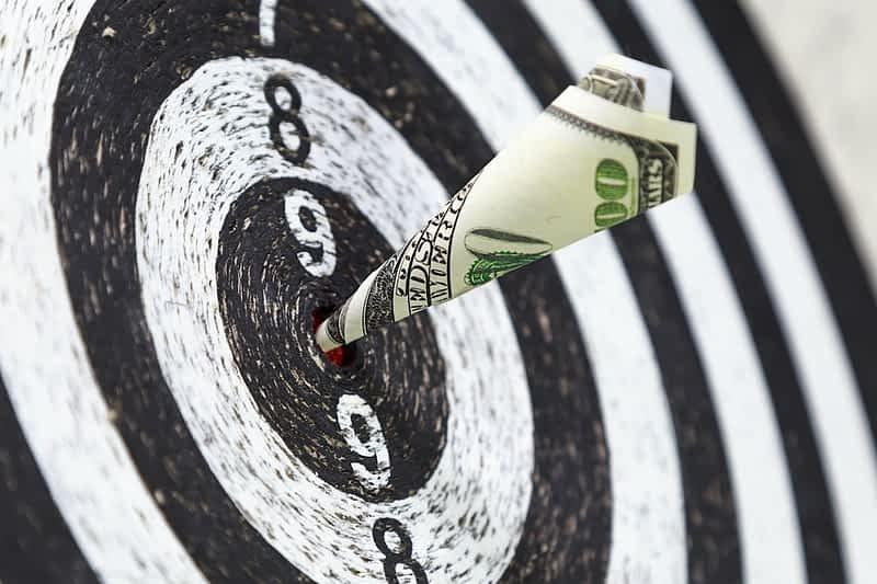 Dart board with 100 dollar bill in the bulls eye