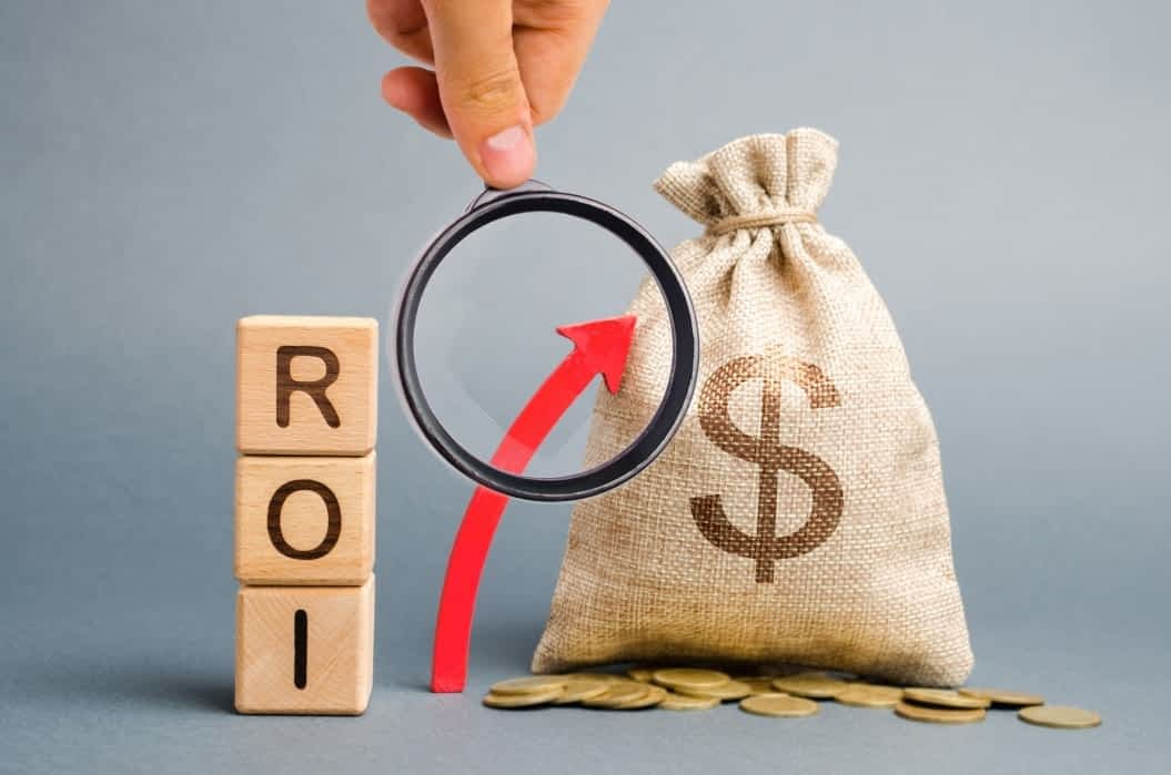 wooden-blocks-with-the-word-roi-and-the-up-arrow-with-the-money-bag-high-level-of-business