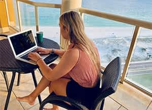woman working-on-writing-a-blog-on-a-laptop-barefoot-on-a-balcony-at-the-beach