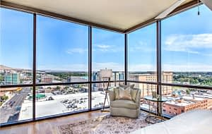 Real estate photography sample of a bedroom with a view of the city scape of Boise Idaho in the windows