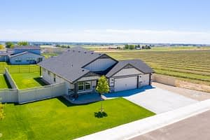 Real estate drone aerial shot of a house next to a field