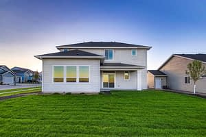 Real estate picture of the back of a house with prominent grass