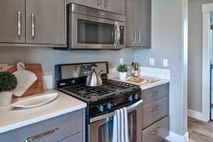 Real estate photograph of a kitchen featuring the stove and microwave