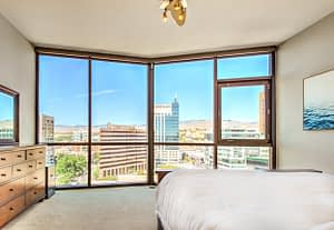 Real estate photography sample of a master bedroom in a high rise building overlooking downtown boise idaho in the windows
