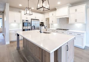 Real estate photography of a bright white kitchen and island